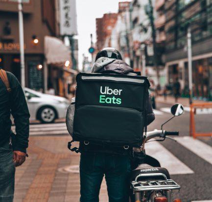Gig worker for Uber Eats preparing to deliver food on his bike