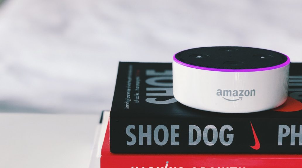 White Amazon Echo Dot turned on that's on top of a pile of books