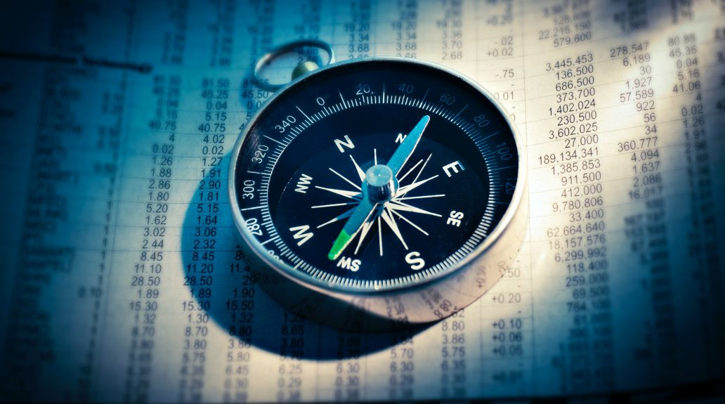 Newspaper listing stocks that has a compass on top