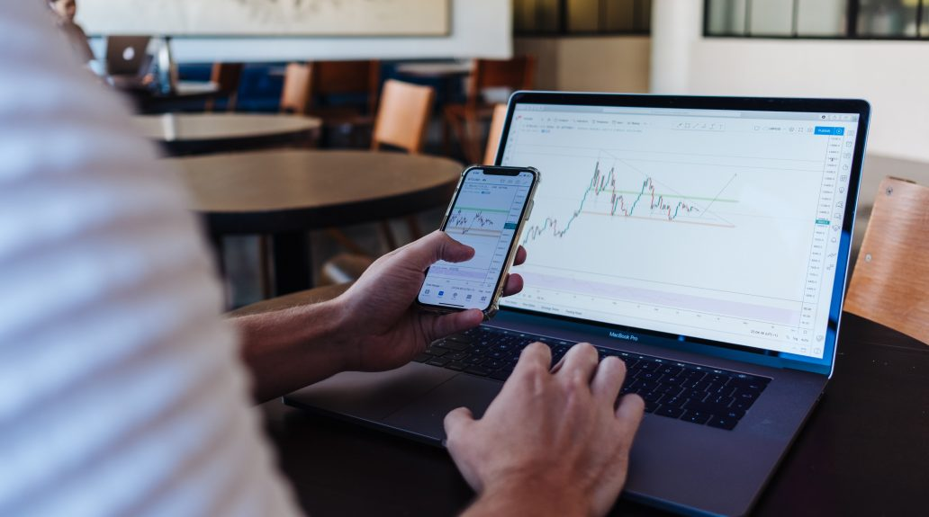 Businessman sitting at a table checking out stocks on his laptop and cell phone