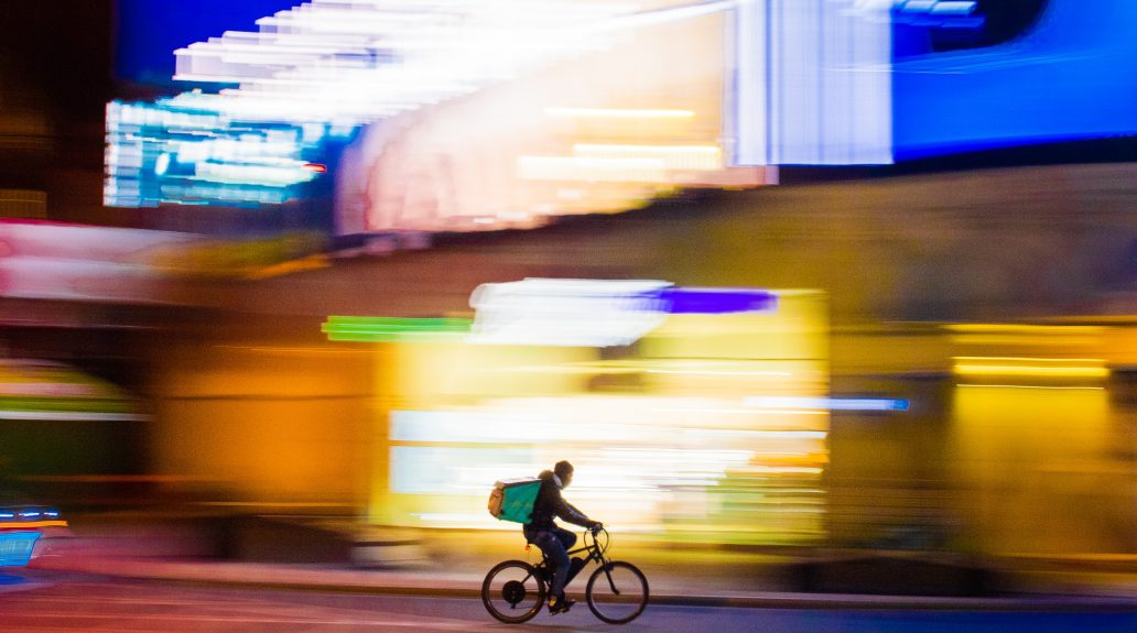 Food delivery courier biking to bring food to customers