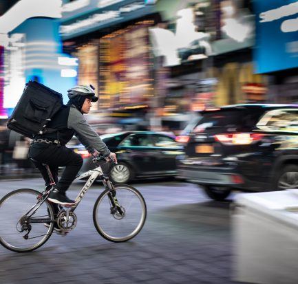 Food delivery courier riding through the city