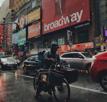 Delivery courier in New York City delivering food in the rain