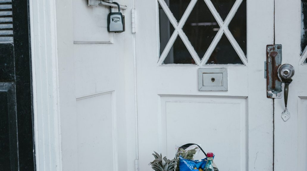 A bag of groceries and package sitting outside an apartment building on the floor